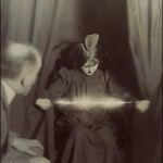 Eva Carriere při materializaci. Materializovaný předmět na její hlavě a zářící zjevení u jejích rukou.